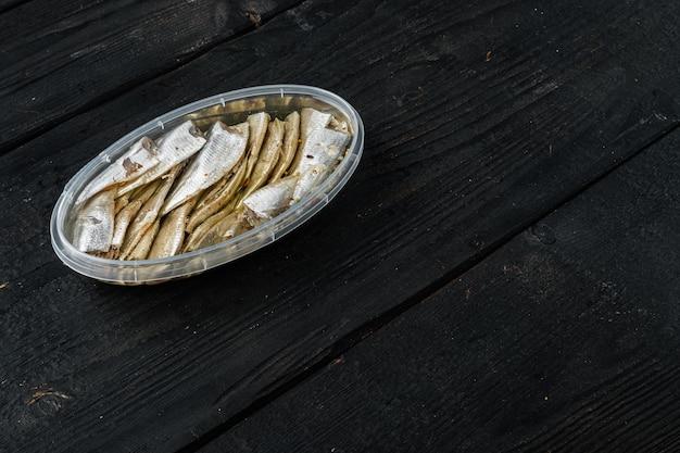 Conjunto de filé de anchovas salgadas em conserva, em recipiente de plástico, sobre mesa de madeira preta