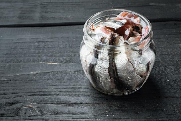 Conjunto de filés de anchova salgada, em frasco de vidro, sobre mesa de madeira preta