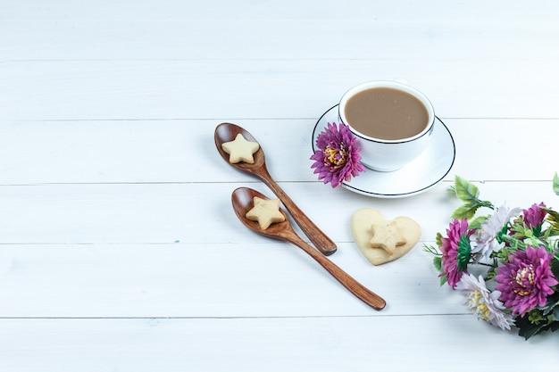 Conjunto de flores, biscoitos em colheres de madeira e café, biscoitos em forma de coração e estrela sobre um fundo branco de placa de madeira. vista de alto ângulo.