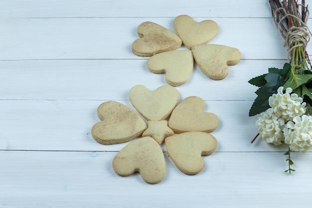 Conjunto de flores e biscoitos em forma de coração em um fundo branco de placa de madeira. fechar-se.
