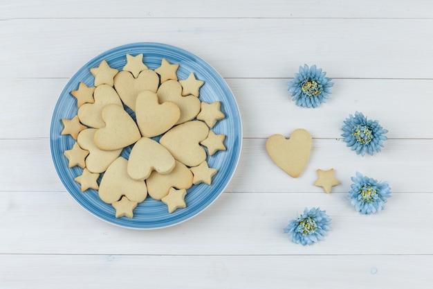 Conjunto de flores e biscoitos em um prato sobre um fundo de madeira. colocação plana.