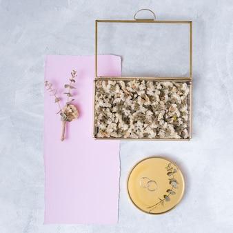 Conjunto de flores em caixa e papel perto de anéis na rodada