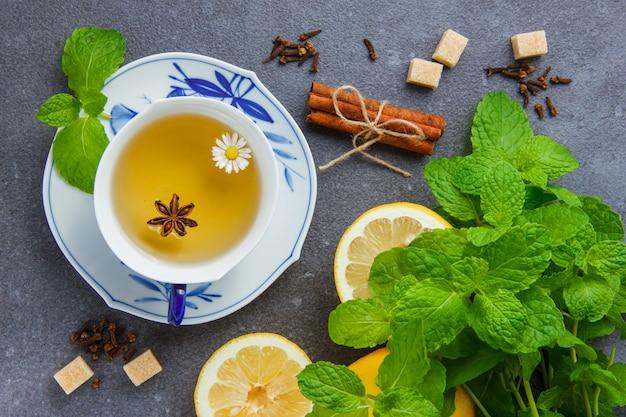 Conjunto de folhas de hortelã, limão, açúcar, canela seca e uma xícara de chá de camomila
