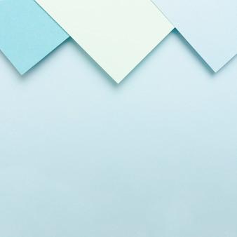 Conjunto de folhas de papel em tons azul com espaço de cópia