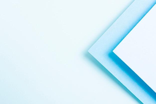 Conjunto de folhas de papel triangular em tons azul com espaço de cópia