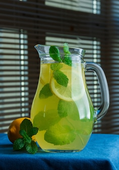 Conjunto de folhas e limão e garrafa de suco de limão na superfície de uma janela preta. vista lateral.