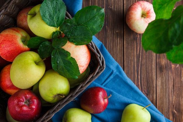 Conjunto de folhas e maçãs em uma caixa em um pano azul e fundo de madeira. configuração plana.