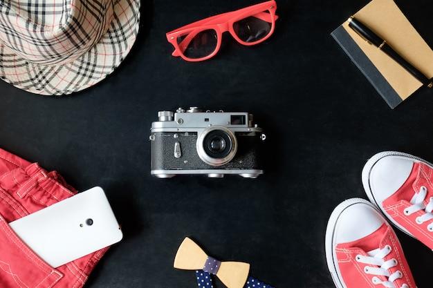 Conjunto de fotografia de filme vintage fineart de tênis vermelho, óculos vermelhos, calça jeans vermelha, câmera vintage, telefone branco, caderno, caneta stylus, chapéu xadrez e gravata borboleta