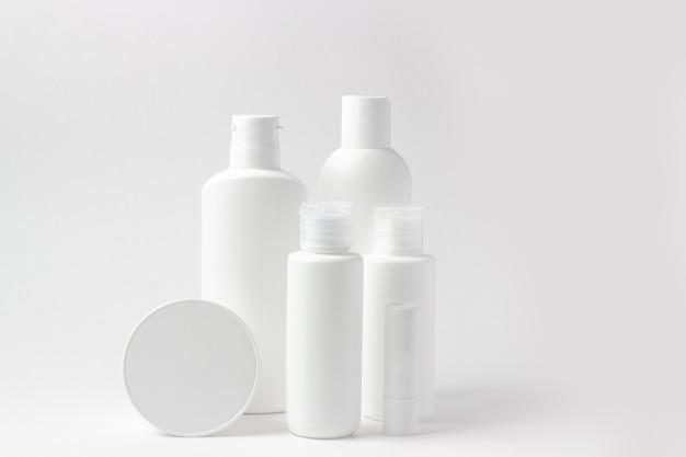 Conjunto de frascos de cosméticos brancos e potes em fundo branco com lugar para adicionar texto