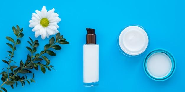 Conjunto de frascos de cosméticos, creme para o rosto e loção sobre um fundo azul com um ramo verde e uma margarida.