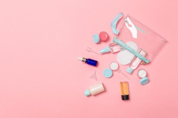 Conjunto de frascos de cosméticos de tamanho de viagem em fundo rosa. postura plana de frascos de creme. vista superior do conceito de estilo bodycare