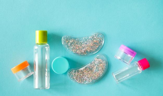 Conjunto de frascos de cosméticos e cremes de tamanho de viagem, almofadas para os olhos em fundo azul menta.
