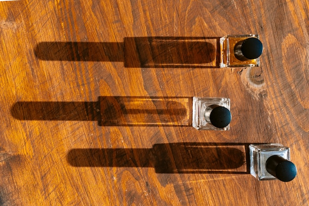 Conjunto de frascos de perfume em uma luz brilhante com sombras