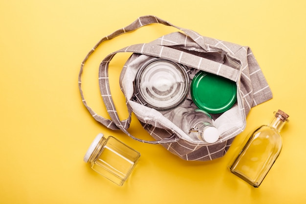 Conjunto de frascos e saco têxtil em fundo amarelo para zero desperdício de compras