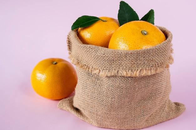 Conjunto de fruta laranja suculenta fresca sobre rosa claro