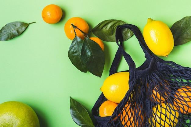 Conjunto de frutas cítricas em saco de malha de têxteis. comida saudável e conceito de desperdício zero.