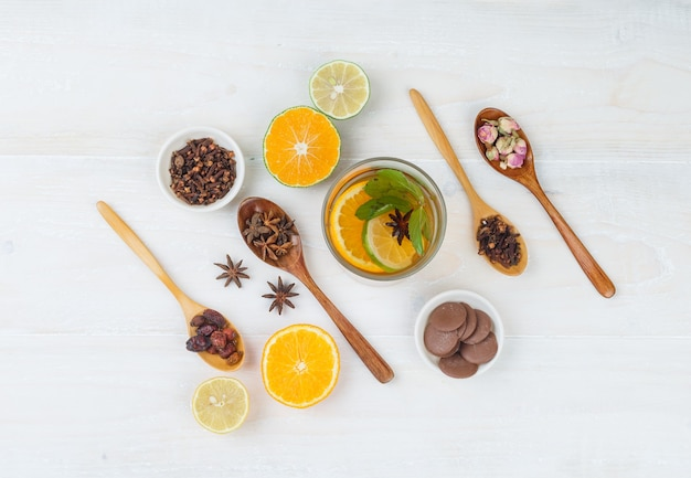 Conjunto de frutas cítricas, panquecas, cravo, frutas secas e botões de rosa e bebida fermentada em uma superfície branca