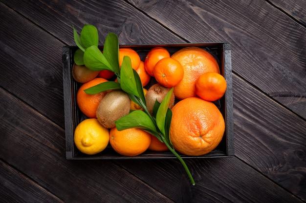 Conjunto de frutas cítricas para aumentar a imunidade em uma caixa preta em um fundo escuro. conceito de aumentar a imunidade.