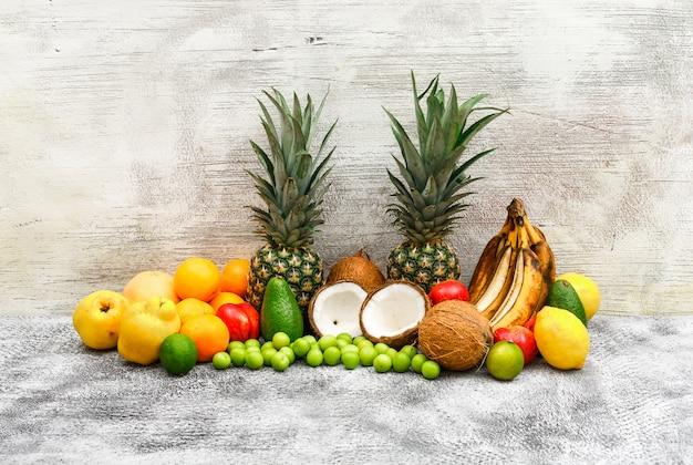 Conjunto de frutas de bananas, abacaxis, cocos, abacates, marmelos, pêssegos, laranjas, ameixas verdes, limões na parede cinza de grunge e madeira. vista lateral.