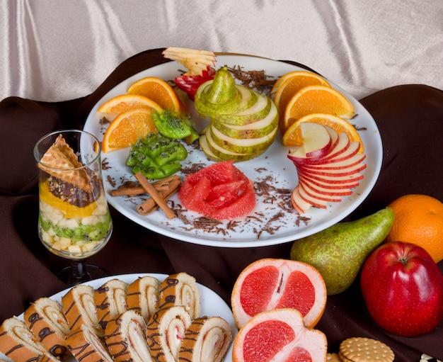 Conjunto de frutas doces e bolo em um fundo de mesa de restaurante