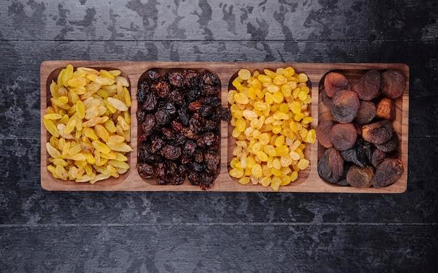 Conjunto de frutas secas, passas, cerejas e damascos em uma bandeja de madeira na vista superior do plano de fundo de madeira preto