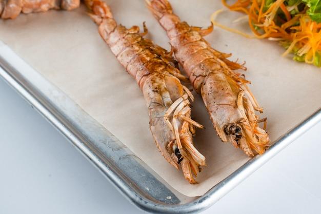 Conjunto de frutos do mar com grandes camarões grelhados na placa de metal com cenoura, close-up de alface.