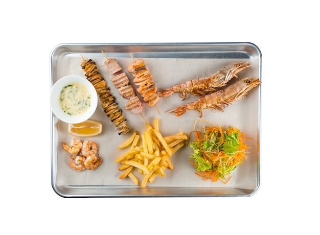 Conjunto de frutos do mar de grandes camarões grelhados, salmão, atum, mexilhões no espeto, salada, batata frita, molho de creme de leite, limão na placa de metal no fundo branco.