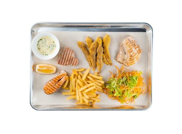 Conjunto de frutos do mar grelhados de atum, peixe branco, salmão, gobies fritos com salada de cenoura, nabo, alface, batata frita, limão, molho de natas com ervas na placa de metal no fundo branco.