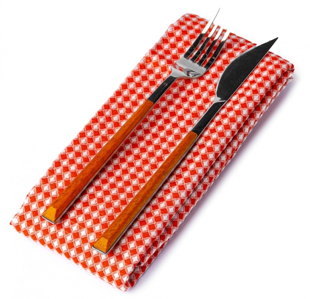 Conjunto de garfo e faca na toalha. isolado no fundo branco vista do topo.