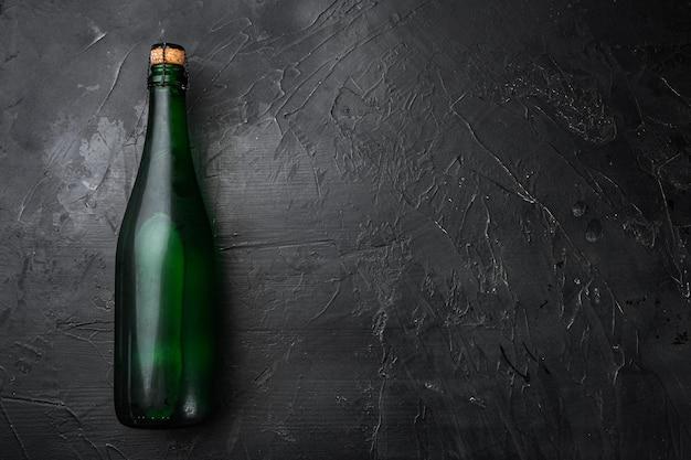 Conjunto de garrafa de água, em fundo de mesa de pedra escura preta, vista de cima plana lay, com espaço de cópia para o texto