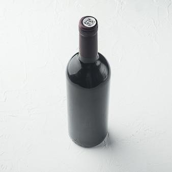 Conjunto de garrafa de vinho, formato quadrado, sobre mesa de pedra branca
