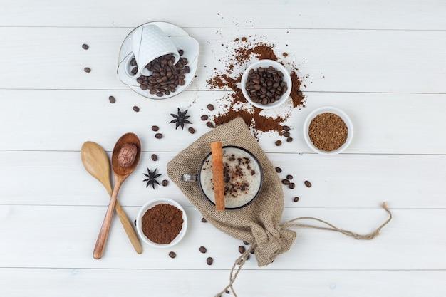 Conjunto de grãos de café, café moído, especiarias, colheres de pau e café em uma xícara com fundo de madeira e saco. vista do topo.