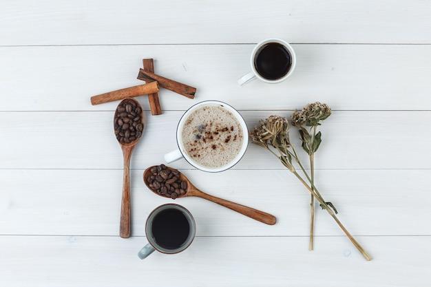 Conjunto de grãos de café, paus de canela, ervas secas e café em xícaras em um fundo de madeira. vista do topo.