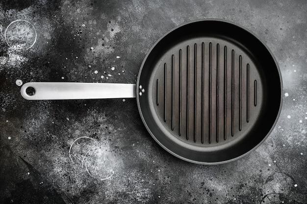 Conjunto de grelha de ferro fundido com espaço de cópia para texto ou comida com espaço de cópia para texto ou comida, vista de cima plana lay, sobre fundo preto de mesa de pedra escura