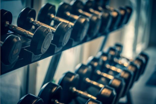 Conjunto de halteres preto. close-up muitos halteres de metal na prateleira no centro de fitness esporte