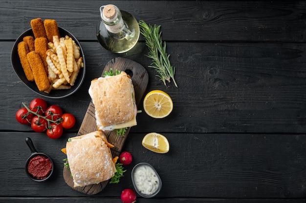 Conjunto de hambúrguer com alface fresca, tomate e molho tártaro de dedos de peixe, numa tábua de madeira, na mesa de madeira preta