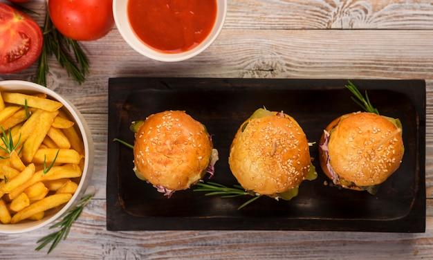 Conjunto de hambúrgueres clássicos com batatas fritas e molho sobre uma mesa