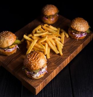 Conjunto de hambúrgueres clássicos com batatas fritas em uma placa de madeira