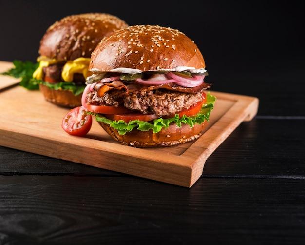 Conjunto de hambúrgueres clássicos em uma placa de madeira