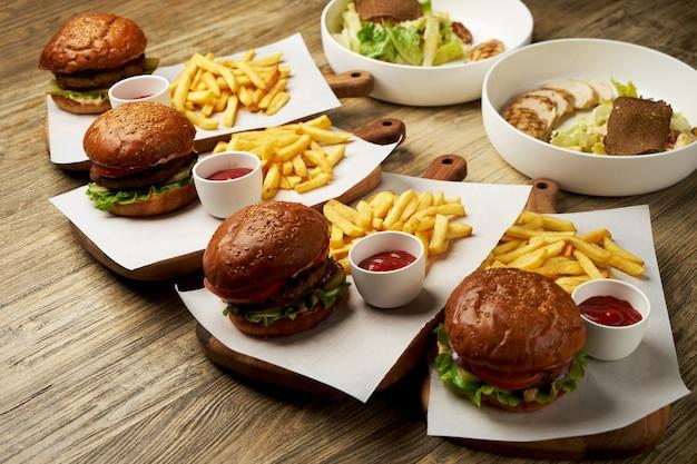 Conjunto de hambúrgueres com batata frita e molho de ketchup. hambúrgueres grandes e batatas fritas no fundo da mesa de madeira. fast-food definir plano de fundo. menu de hambúrguer do restaurante