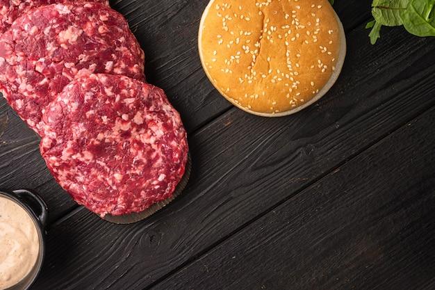 Conjunto de hambúrgueres de bife picado cru de carne de vaca, na mesa de madeira preta