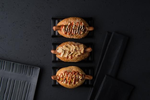 Conjunto de hambúrgueres em pratos planos em fundo preto, vista superior
