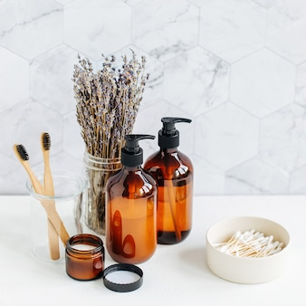 Conjunto de higiene pessoal com lavanda. frascos de sabonete e shampoo na mesa branca no fundo do banheiro.