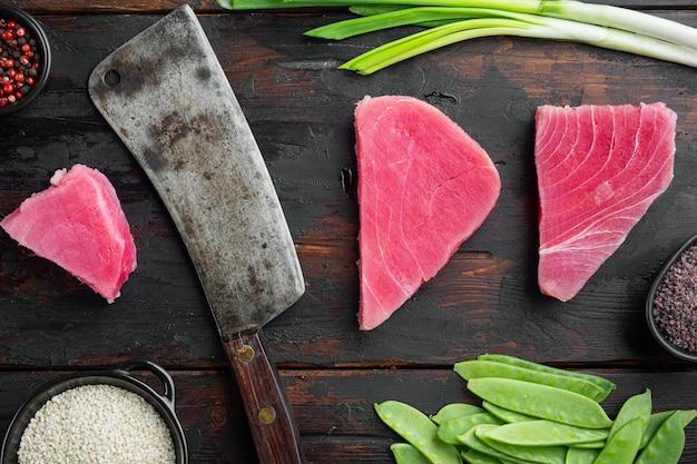 Conjunto de ingredientes de bife de atum com gergelim cru e faca de cutelo de açougueiro, no fundo da mesa de madeira escura velha, vista de cima plana lay