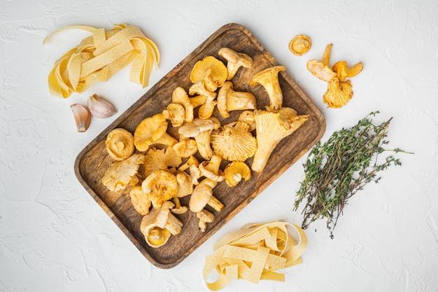 Conjunto de ingredientes de cogumelos macarrão chanterelle, no fundo da mesa de pedra branca, vista de cima plana lay
