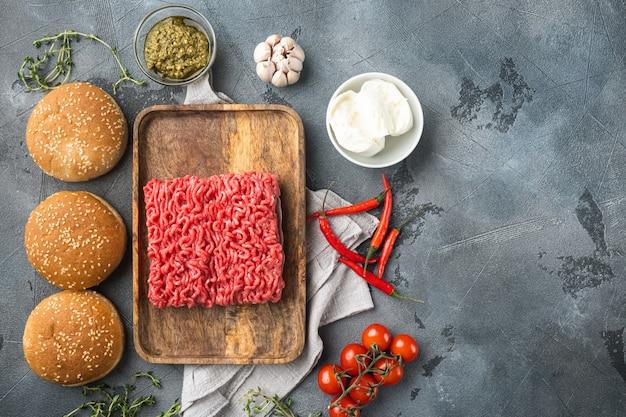 Conjunto de ingredientes de hambúrgueres de carne picada crua em casa, em uma bandeja de madeira, em uma mesa de pedra cinza, vista de cima plana