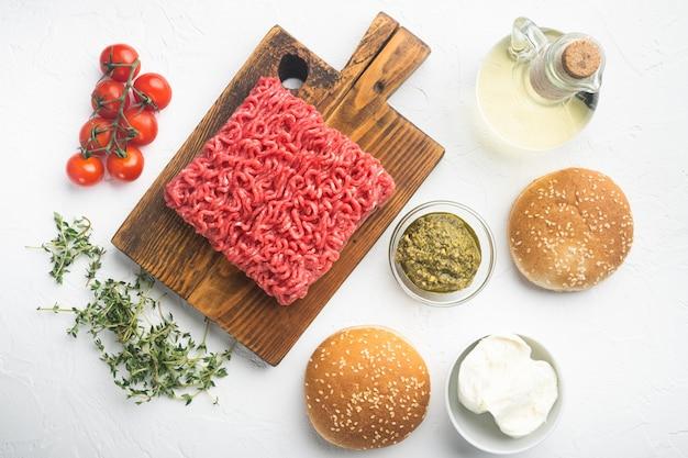 Conjunto de ingredientes de hambúrgueres de carne picada crua em casa, em uma tábua de madeira, em uma mesa de pedra branca, vista de cima plana