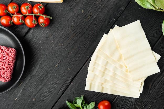 Conjunto de ingredientes de lasanha de carne, na mesa de madeira preta