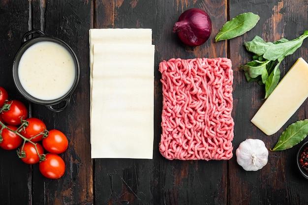Conjunto de ingredientes de lasanha de carne, na velha mesa de madeira escura, vista de cima, plano plano