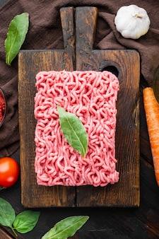 Conjunto de ingredientes de molho à bolonhesa, tomate de carne picada e ervas, numa tábua de madeira, na velha mesa de madeira escura, vista superior, plana leiga